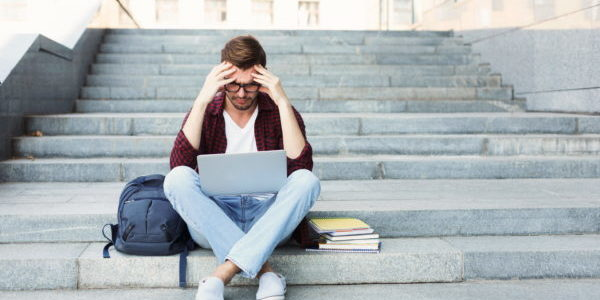 Desperate student sitting on stairs with laptop