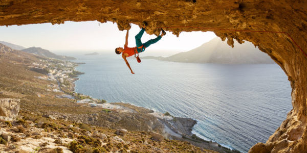Male rock climber on challenging route going along ceiling in ca